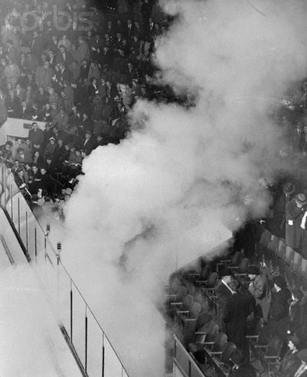 """17 Mar 1955, Montreal, Canada --- Smoke rising from a tear gas bomb drifts through the Forum arena March 17 as 15, 000 demonstrators angrily protest the suspension of Maurice """"The Rocket"""" Richard by National Hockey League President Clarence Campbell. The bomb was set off by a demonstrator at the intermission between the first and second periods. It was at this point that Fire Chief Armand Pare ordered the game halted for the """"protection of the people."""" Montreal trailed at the time, 4-1, and that was declared the final score. The calm of the spectators in the upper seats, which were unaffected by the bomb's fumes, prevented crushing at the exits. --- Image by © Bettmann/CORBIS"""